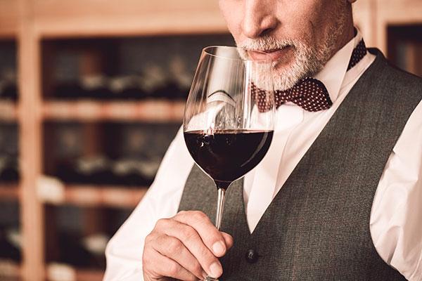 homem segurando uma taça de vinho tinto pela haste