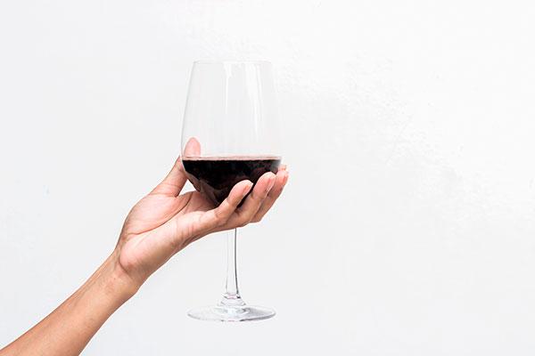 Mão segurando uma taça de vinho pelo bojo