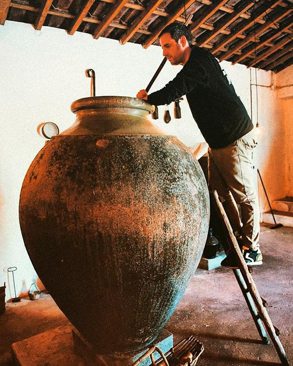 Pedro Ribeiro mistura o mosto dentro da enorme talha de barro